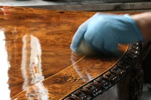 Instructor wearing gloves French polishing a wooden table